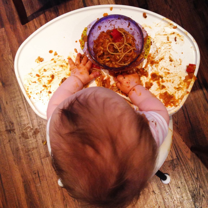 baby in high chair eating spaghetti bolognaise with fingers - quite messy