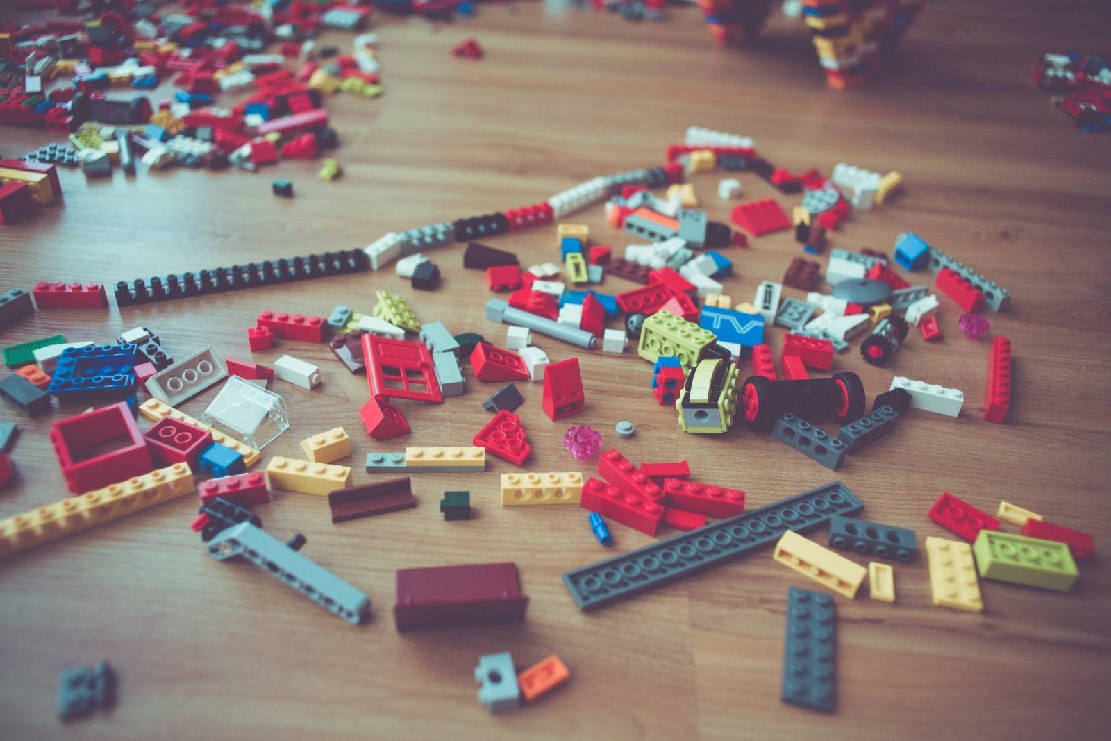 differed coloured lego bricks lying messily on wooden floor